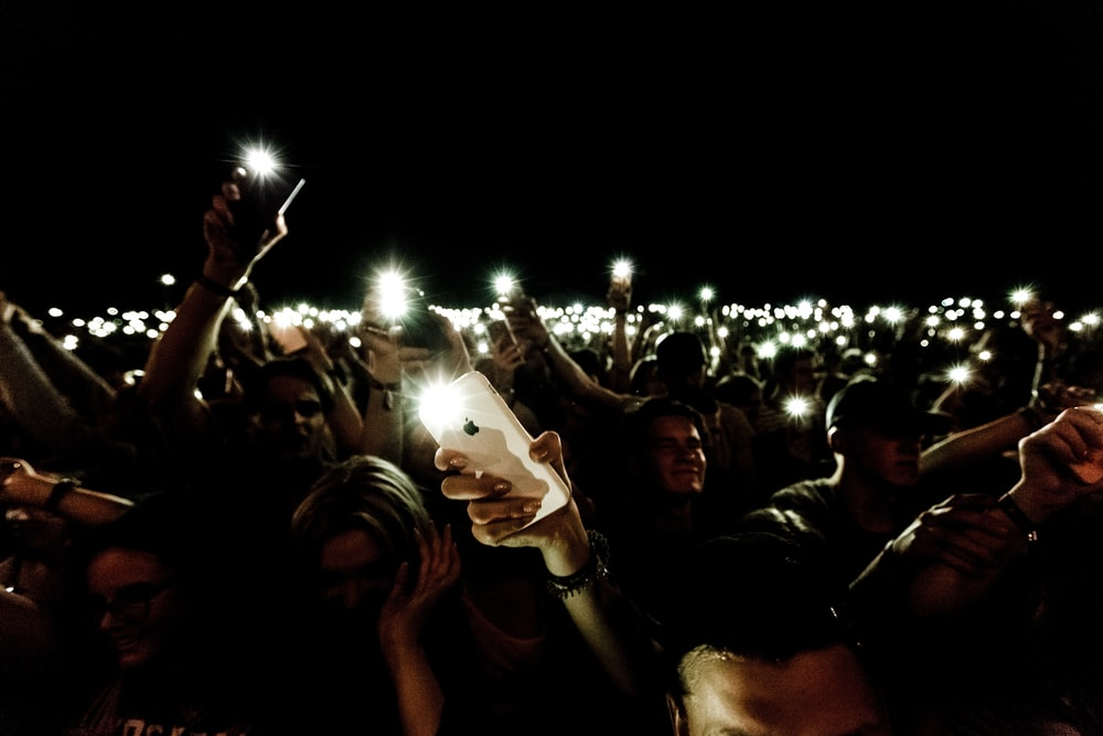 crowd holding smartphone while in flashlight
