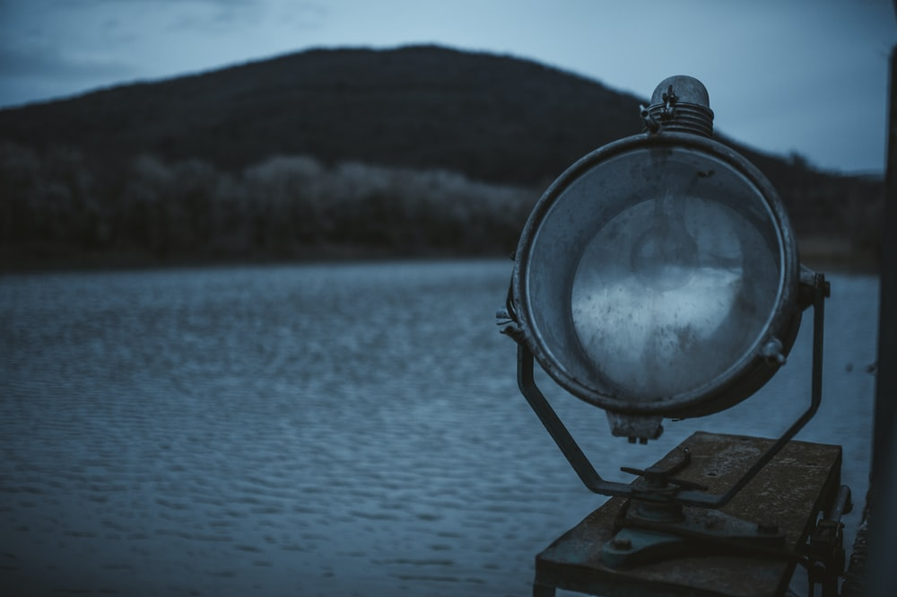 selective focus photography of gray light near body of water