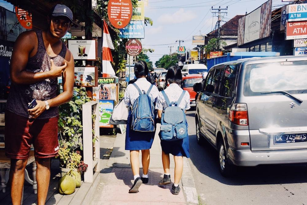 two girls walking on sidewalk during daytime