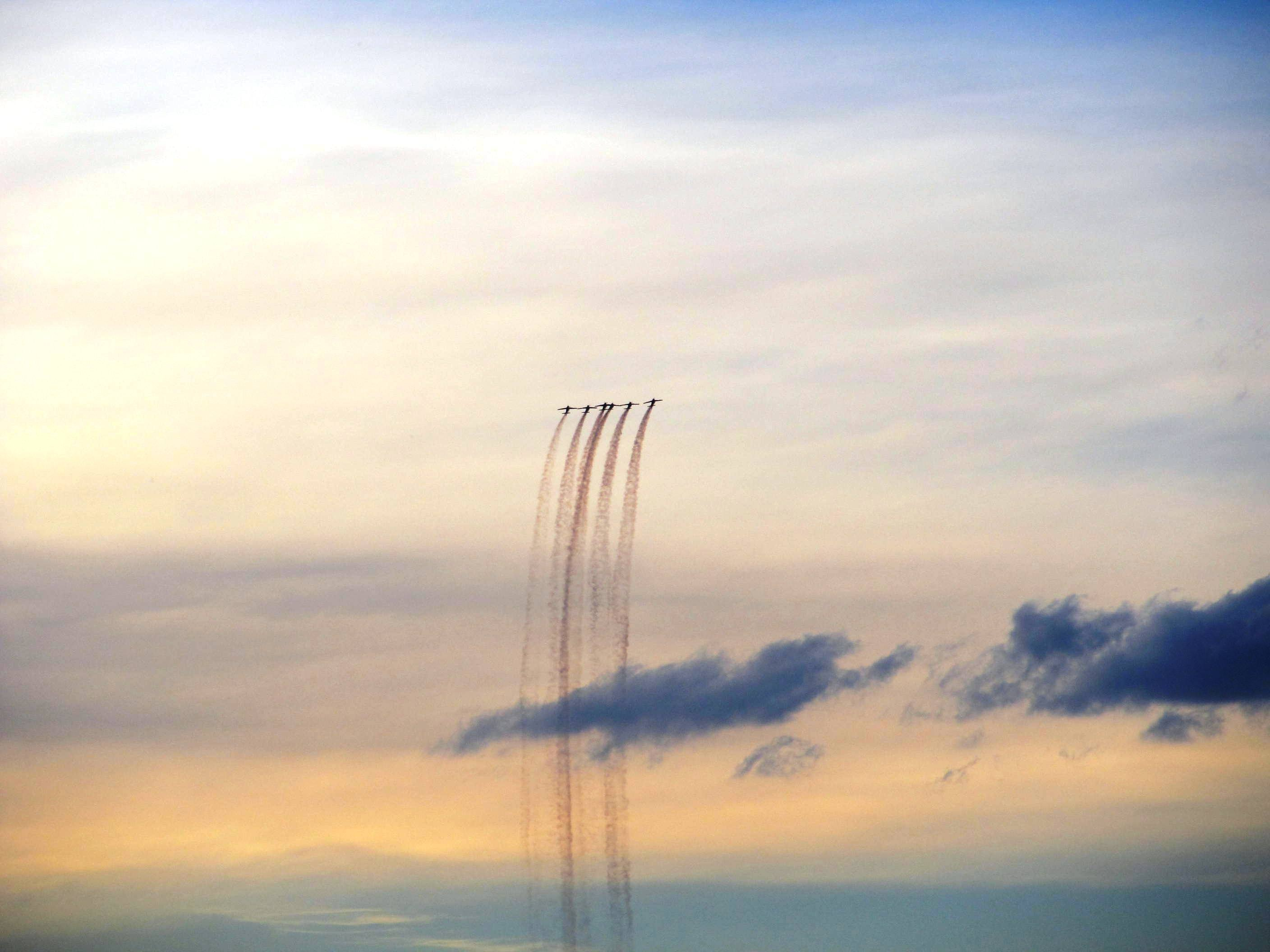 several plane doing stunts during sunset