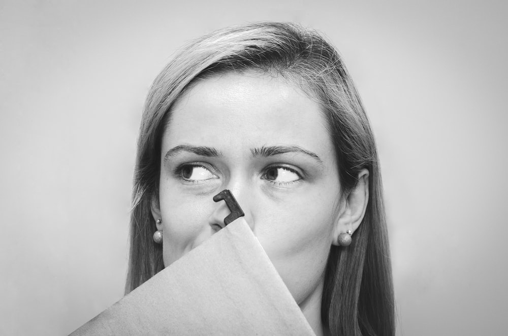 grayscale photography of woman with earrings covering her mouth