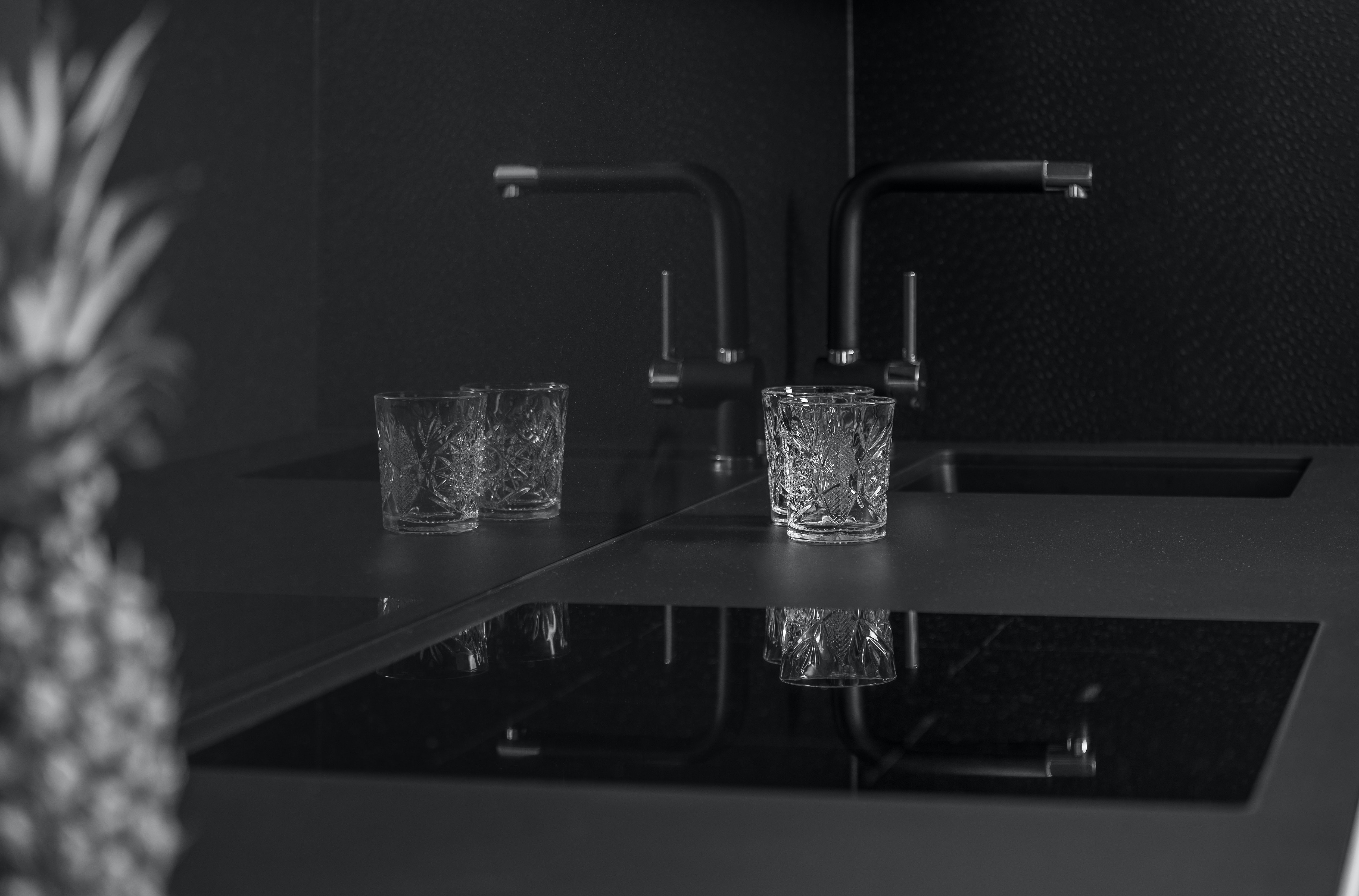 grayscale photo of two rocks glass near sink