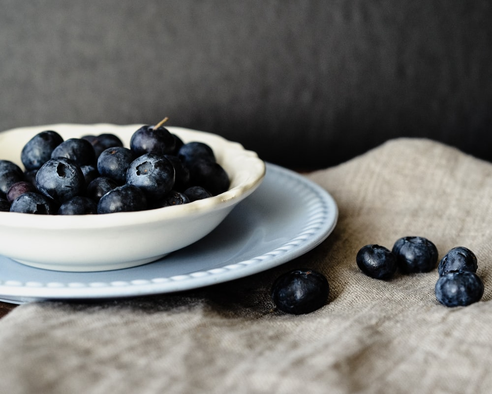blue berry fruit on top of white owl