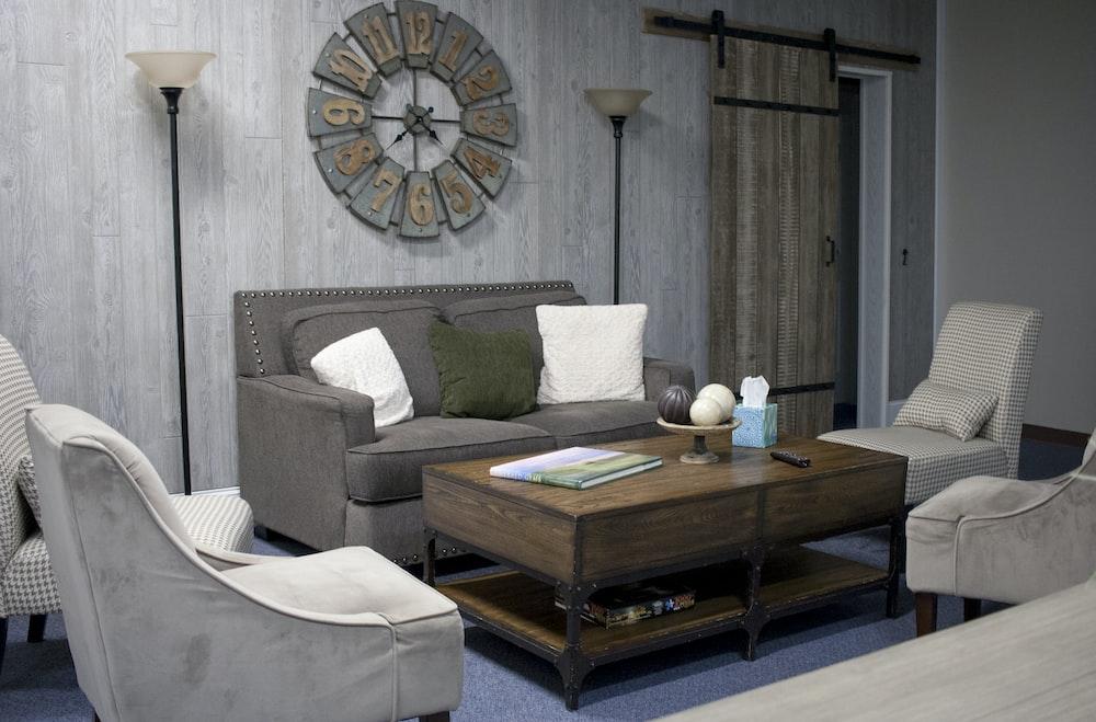 two white throw pillows on top of grey sofa