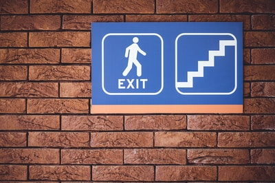 blue and white exit signage mounted on brown brick wall
