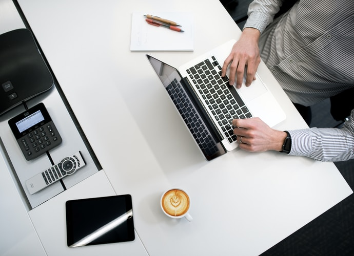 person using laptop on white wooden table