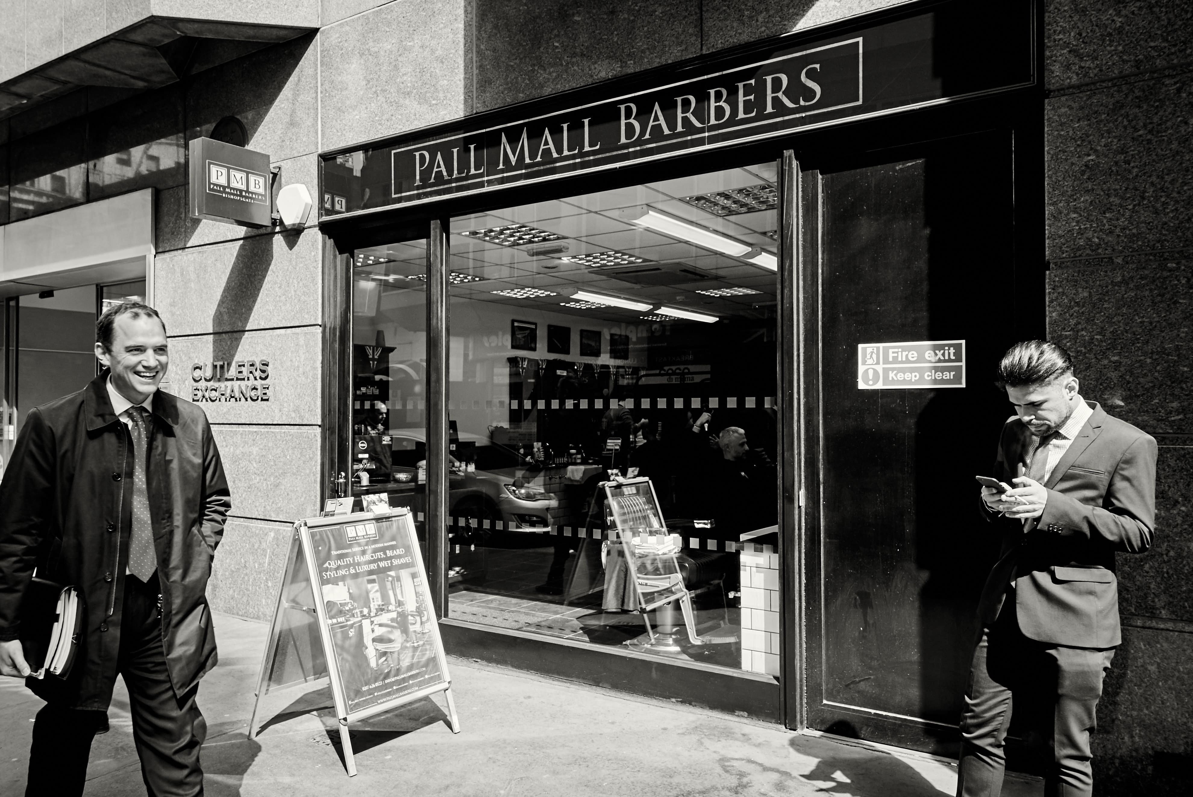 grayscale photo of people standing near Pall Mall Barbers