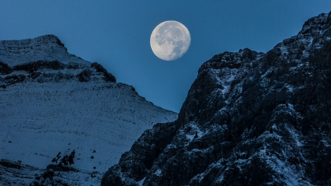 Moon setting behind the mountains in Canmore, Alberta