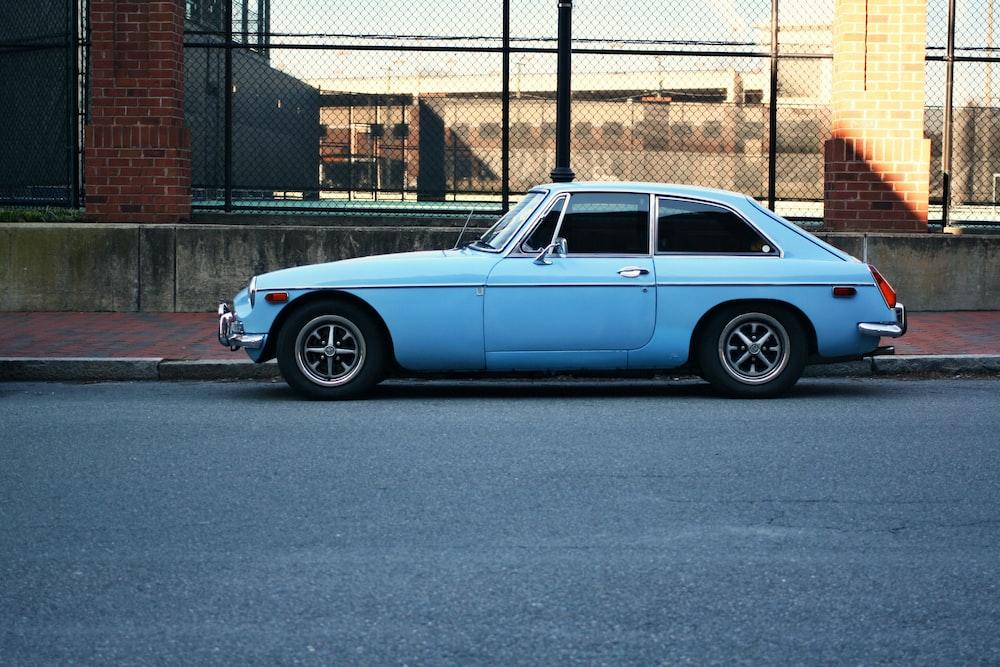 blue classic 3-door hatchback on gray concrete road