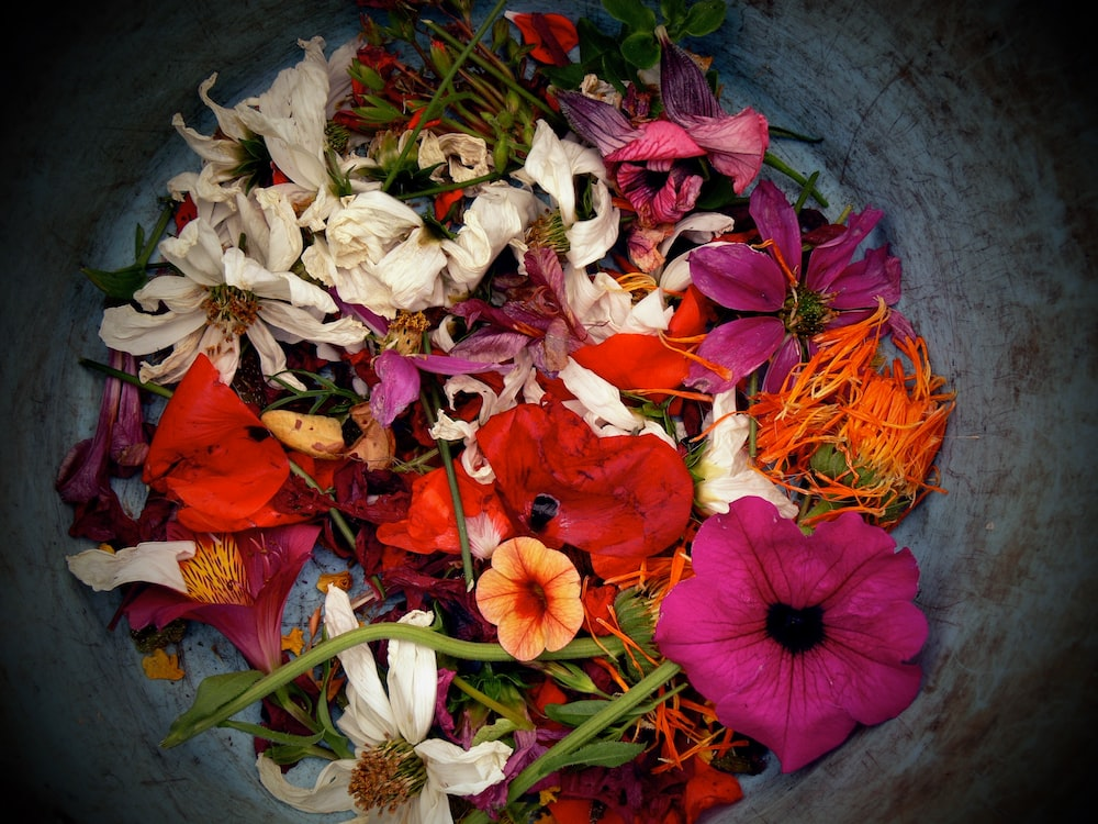 assorted flowers piled in container