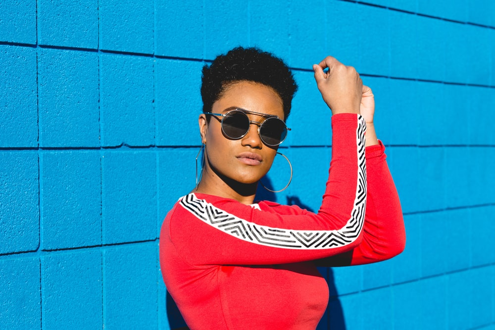 woman wearing red long-sleeved shirt leaning of blue wall