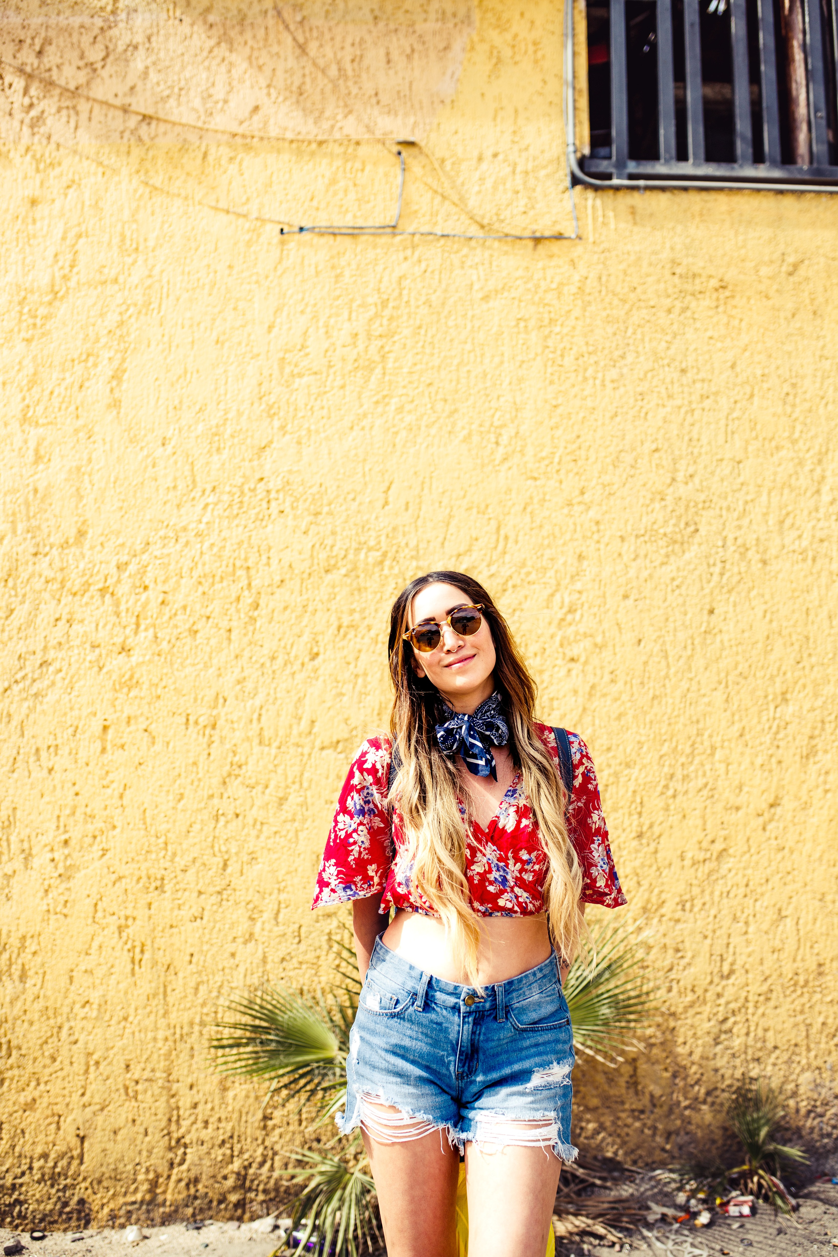 woman in red floral crop-top and blue denim shorts standing in front of brown concrete house during daytime