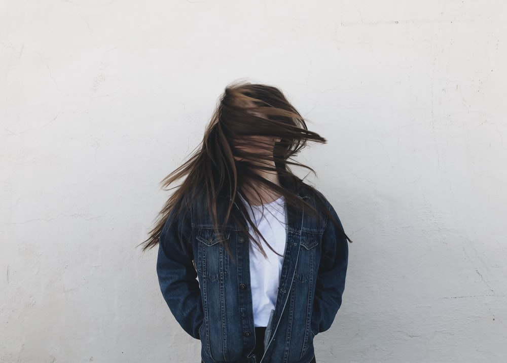 woman wearing blue denim jacket standing near white concrete wall