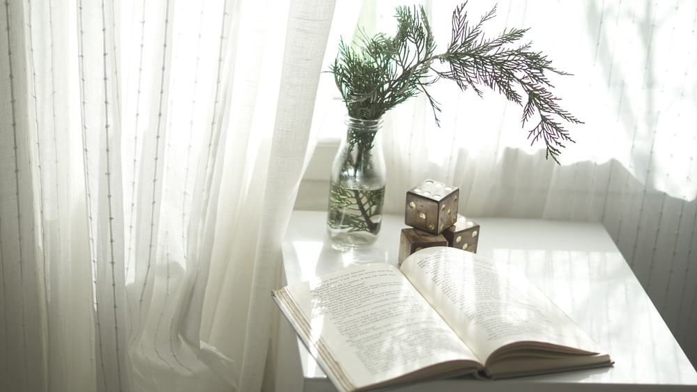 book opened on top of white wooden table