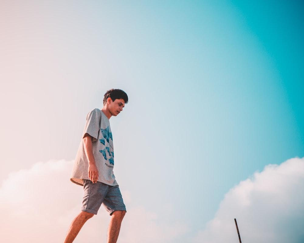 man in gray crew-neck shirt walking
