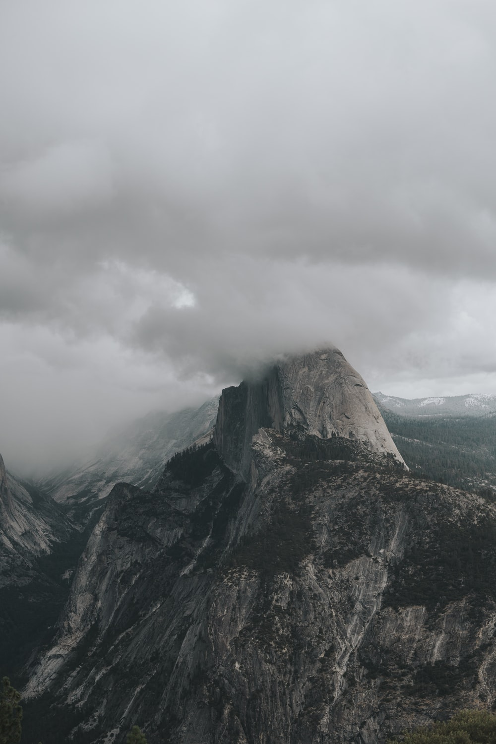 gray and green mountain under gray clouds