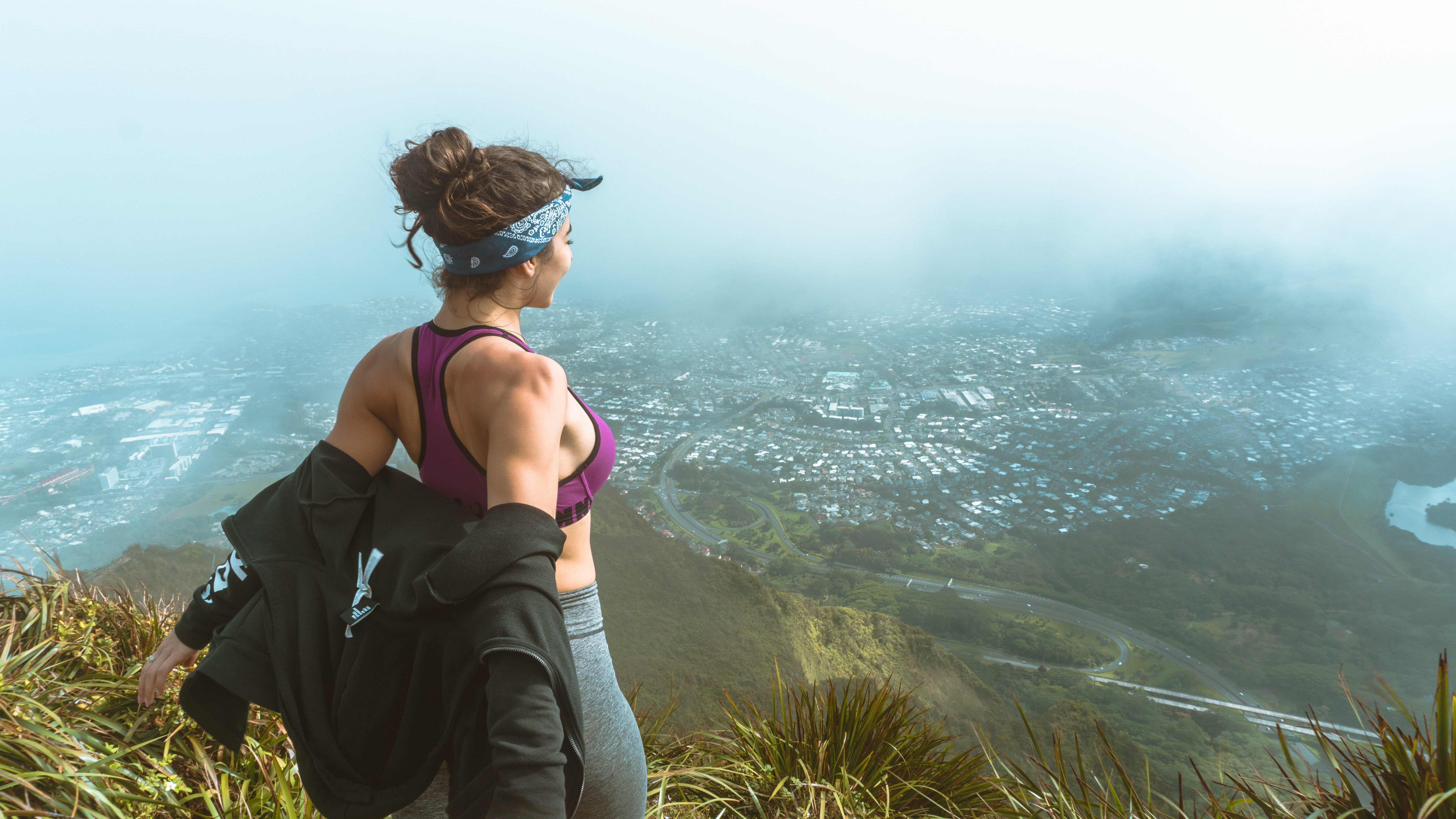 woman in pink sports bra and grey leggings overlooking city skyline from a mountain with fogs during daytime