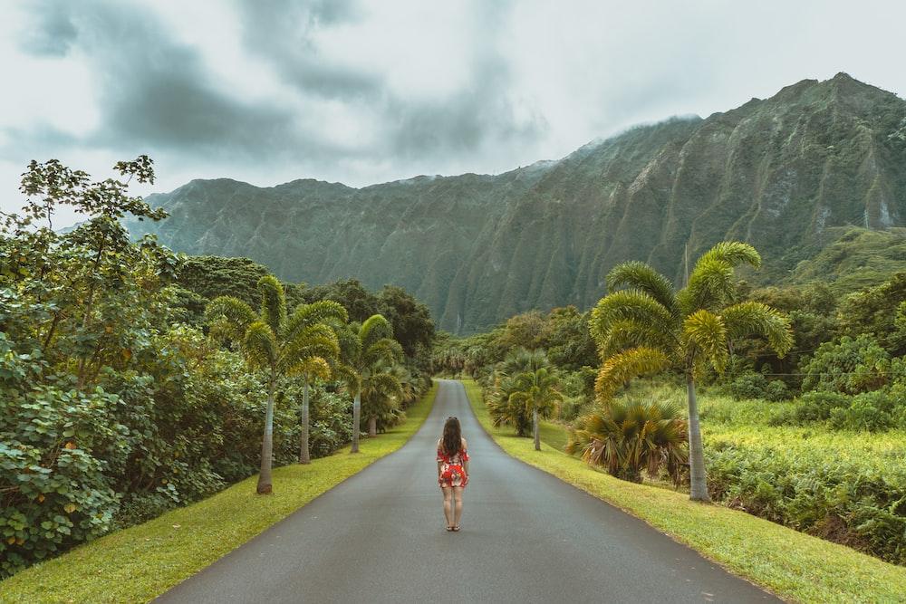 woman walking in black concrete road in front of mountain