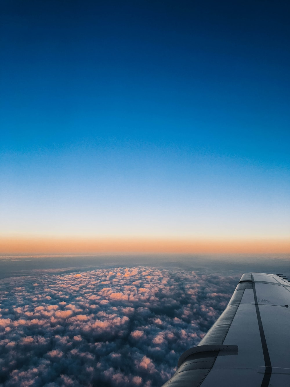 plane flying on top of white clouds
