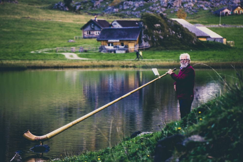 woman holding elongated wind instrument at the lake