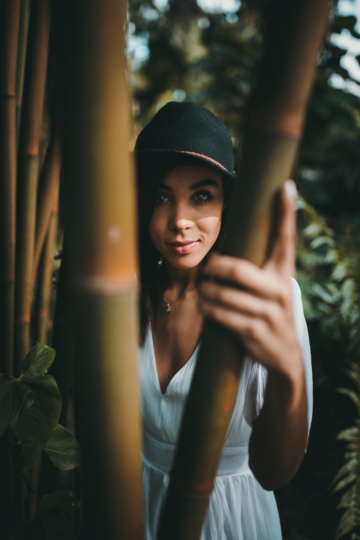 standing woman wearing white dress holding bamboo