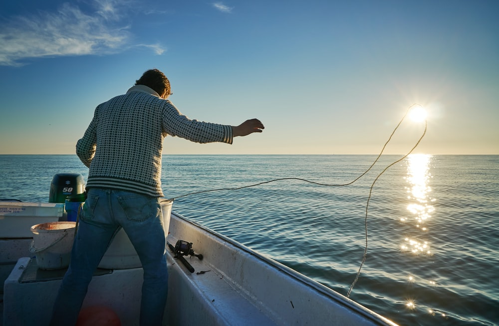 man standing on boat throwing rope on water