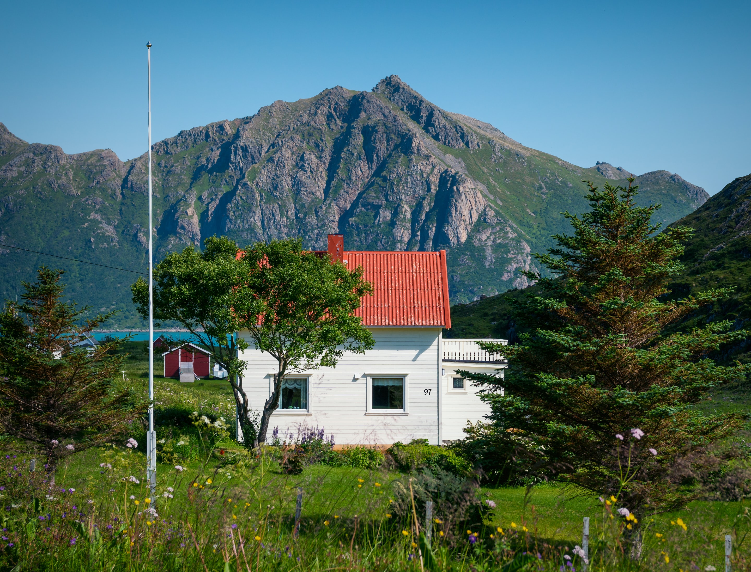 white and red concrete house near mountain
