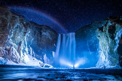 person in front of waterfalls during nighttime waterfall teams background