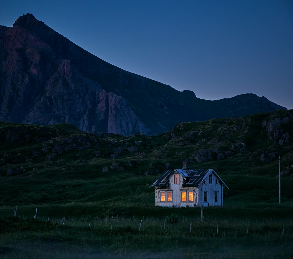 lighted house on green field