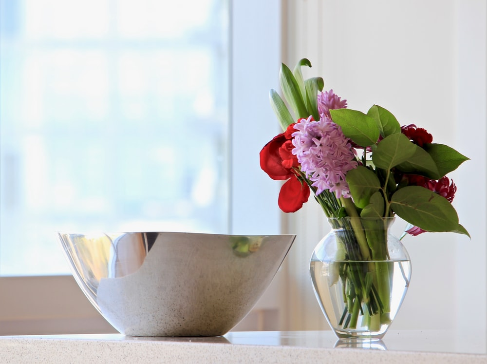 gray stainless steel bowl beside red and pink petaled flower centerpiece