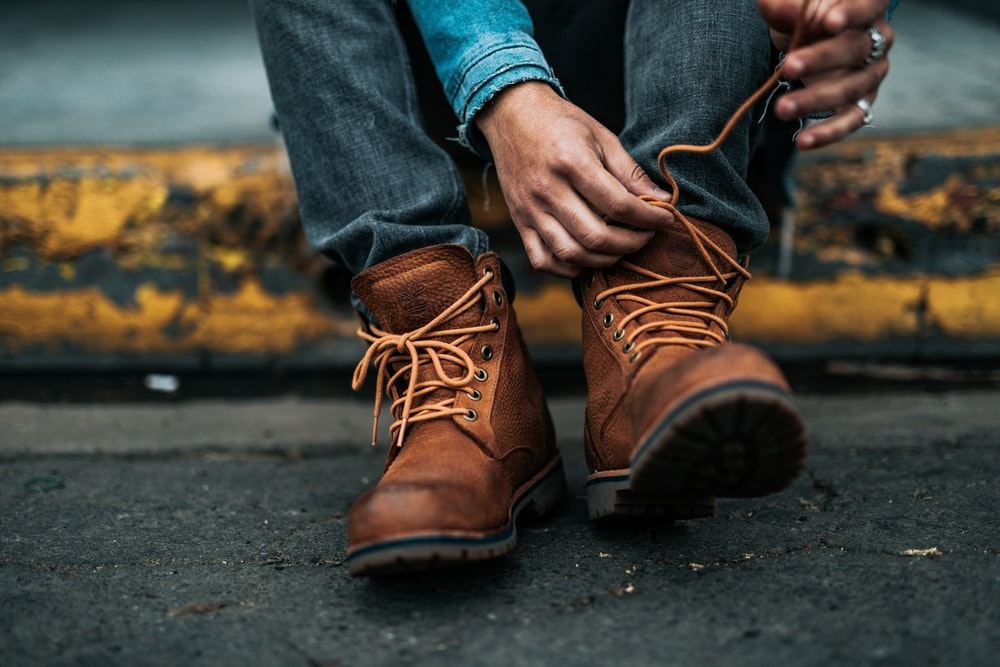 person sitting on yellow gutter tying up his left boot's laces