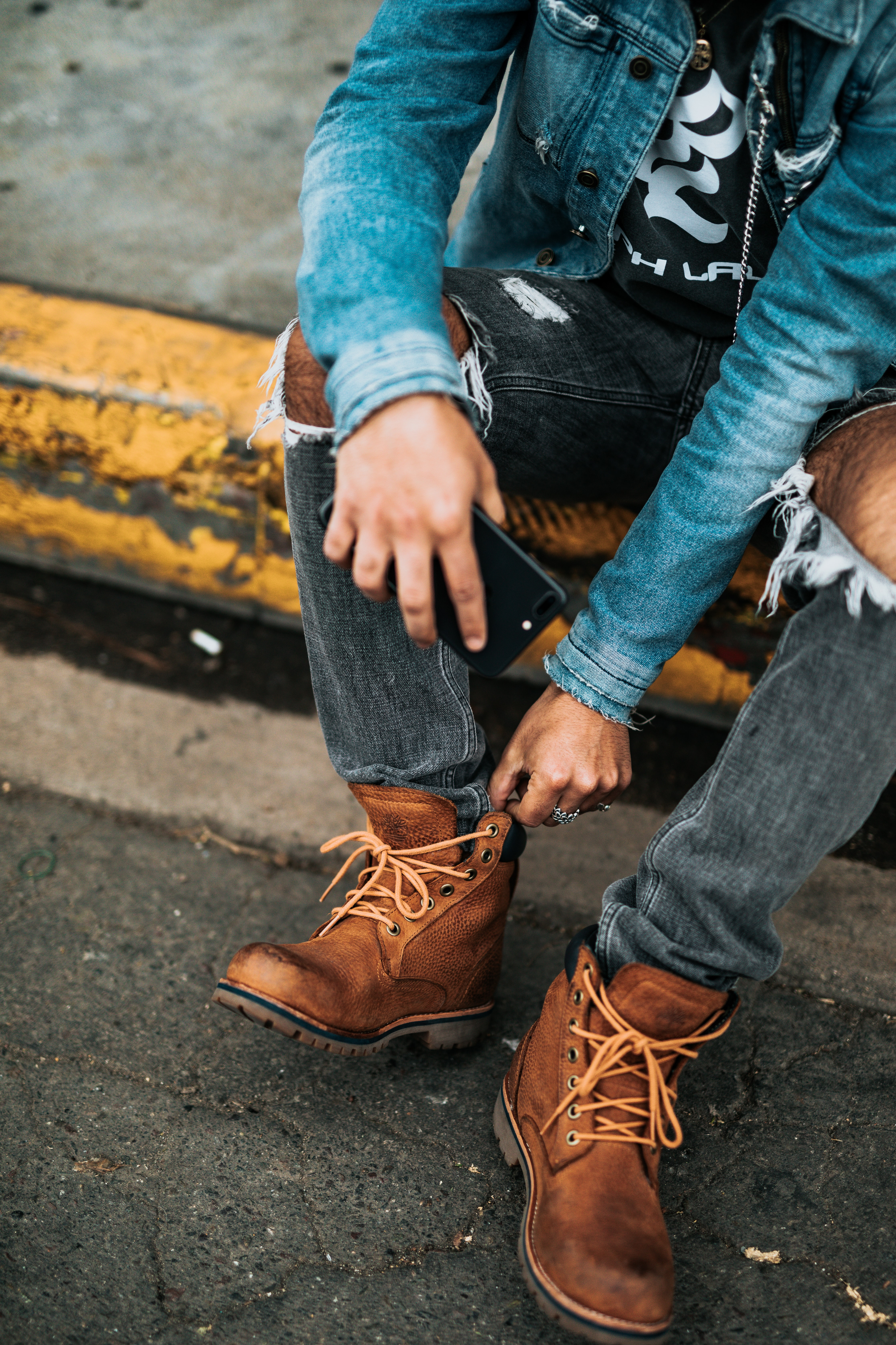 person wearing pair of brown boots, distressed fitted jeans, and denim jacket