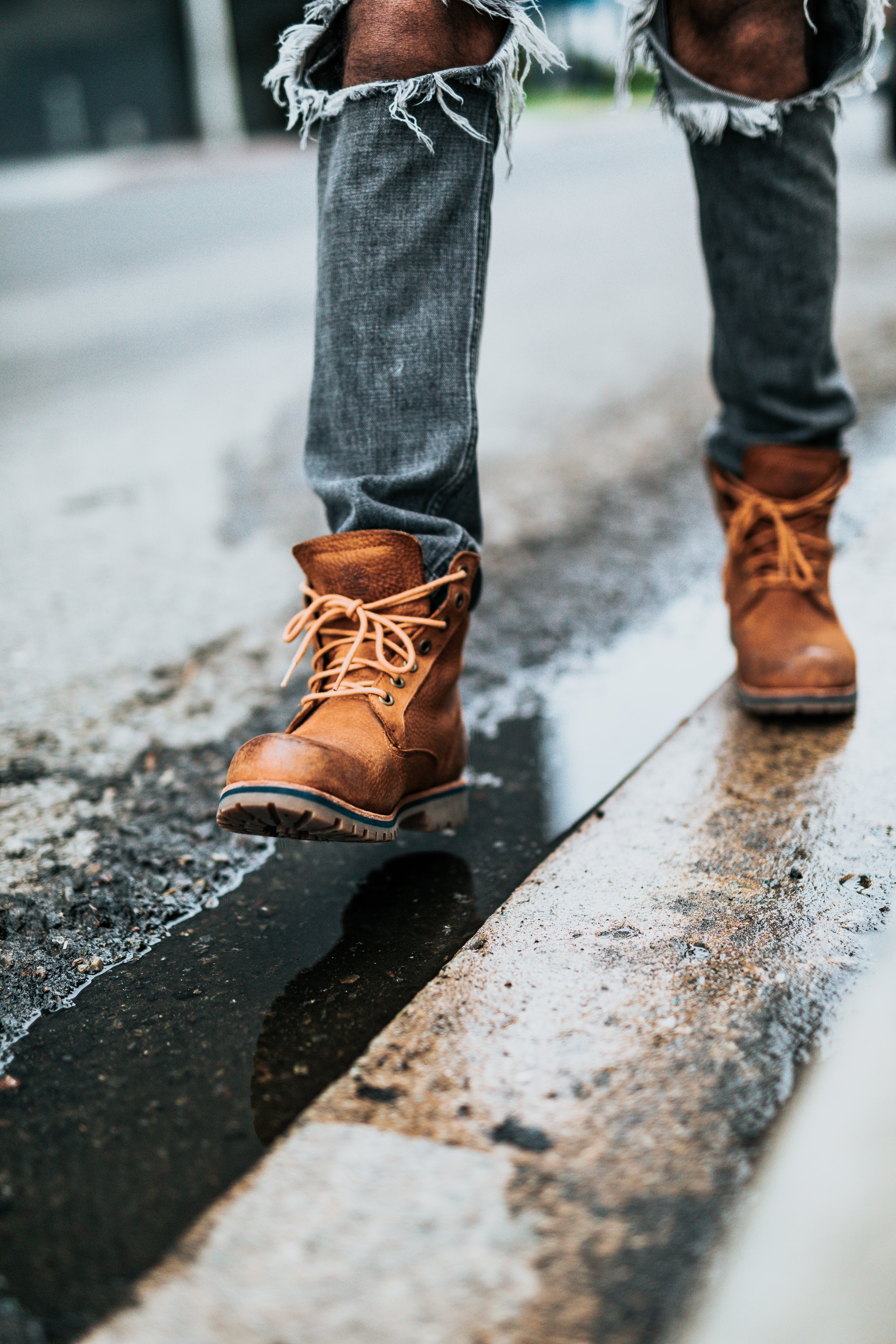 person in gray jeans and brown leather boots walking on road