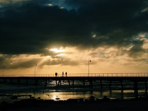 silhouette of four people standing on sea dock