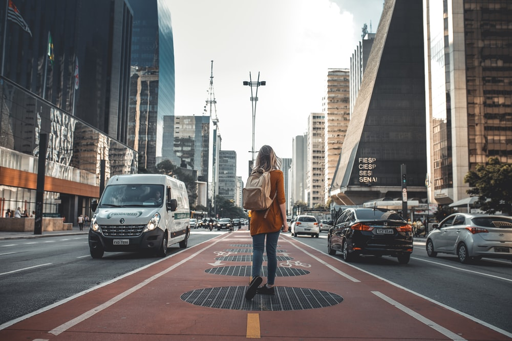 photography of woman walking in between road with vehicles