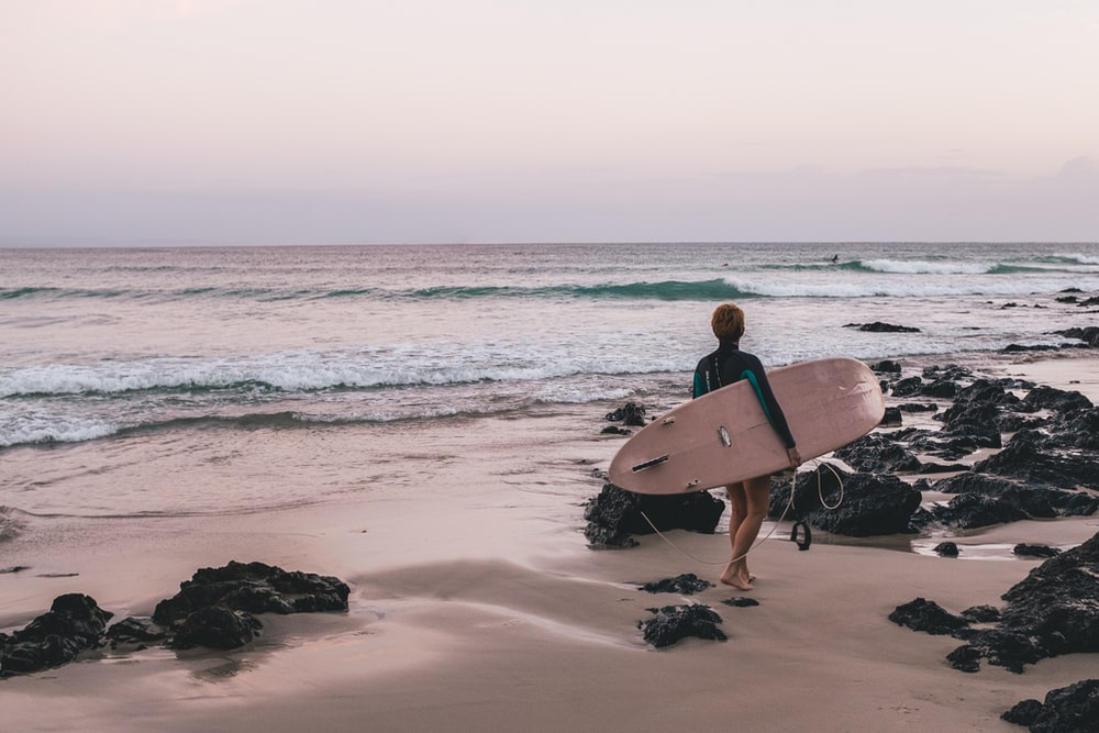 woman carrying surfboard on the seashore