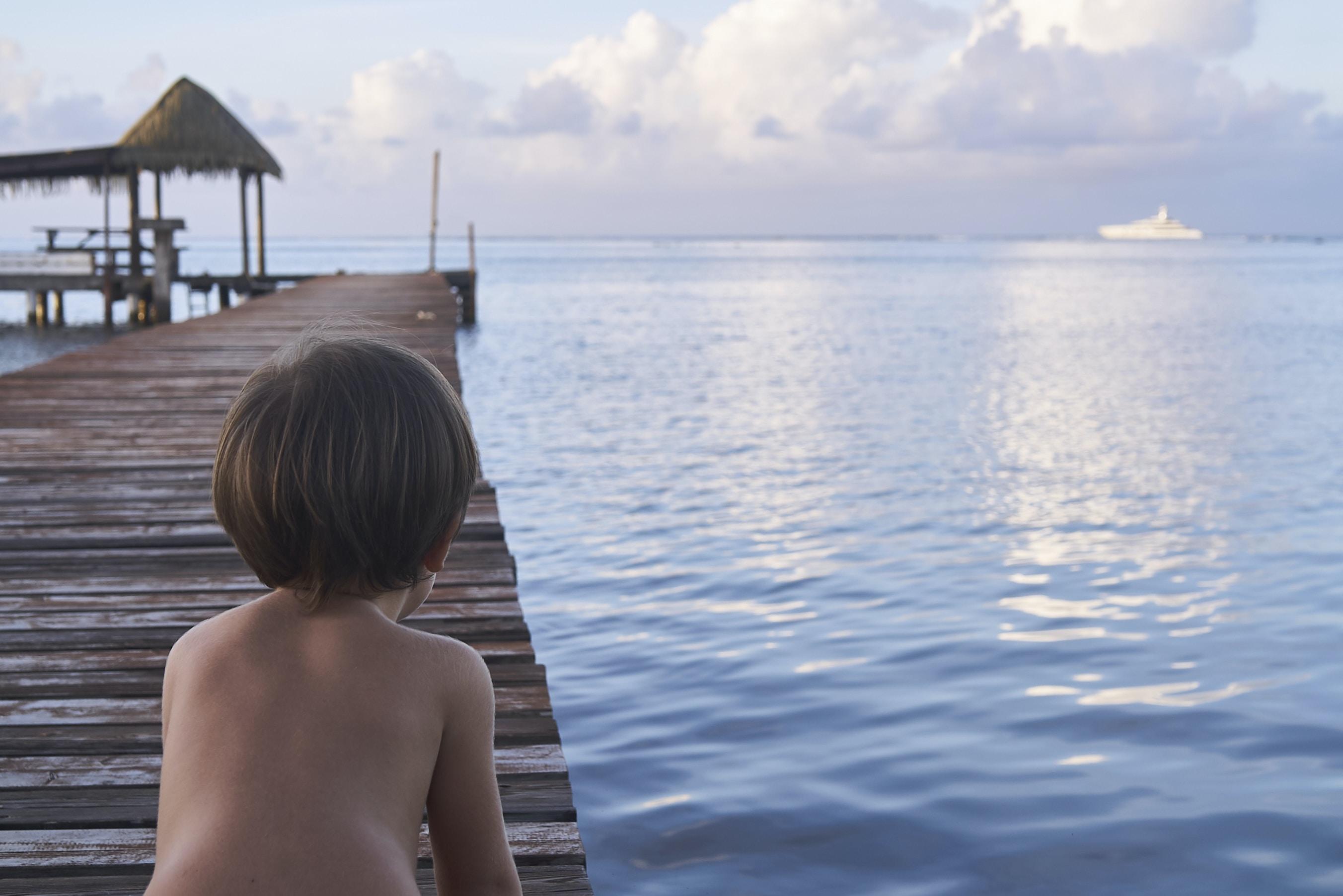boy kneeling on wooden dock
