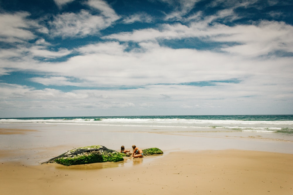 photo of two women on shore under cloudy sky
