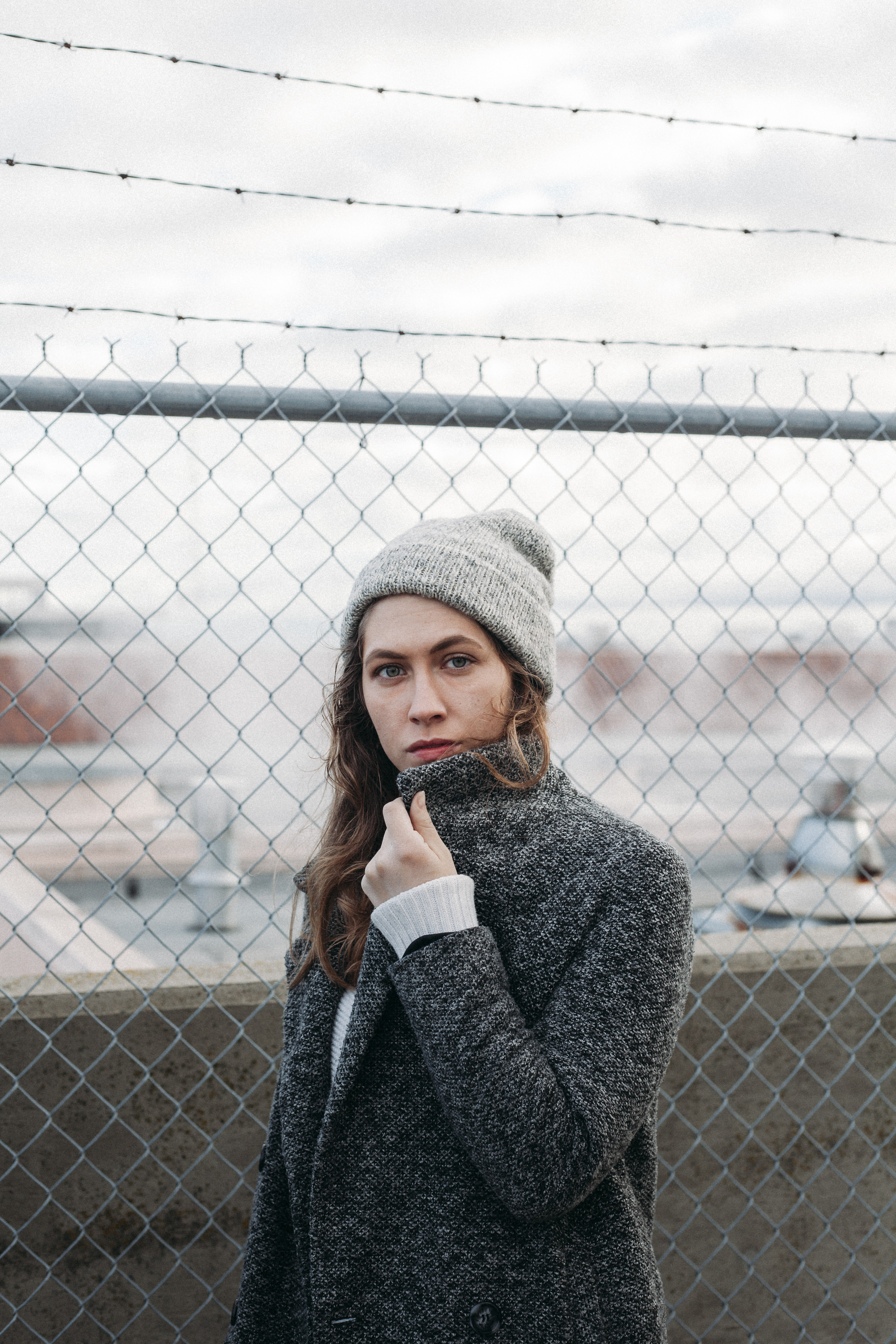 woman standing near gray steel chain link fence