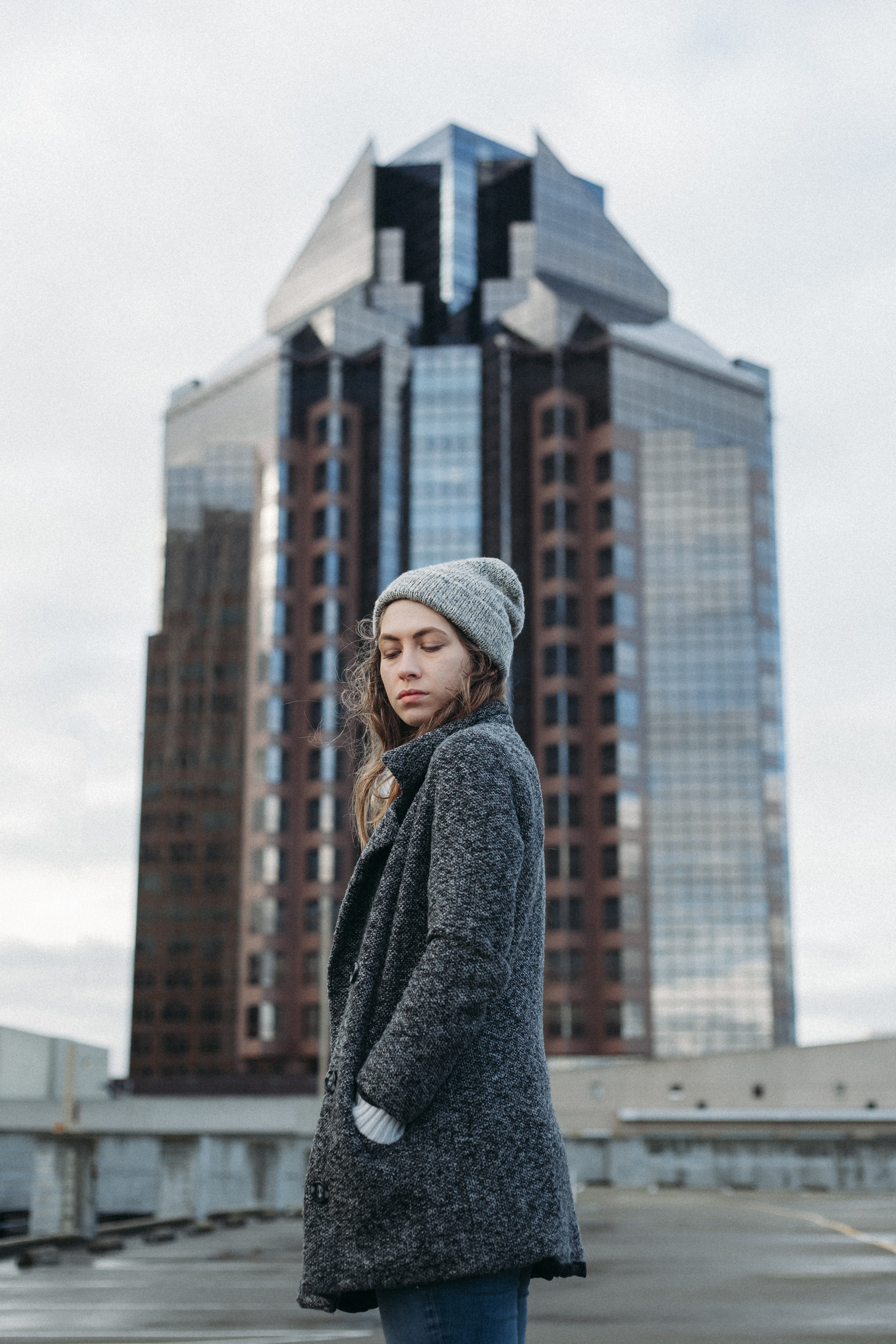 woman standing behind high rise building during daytime
