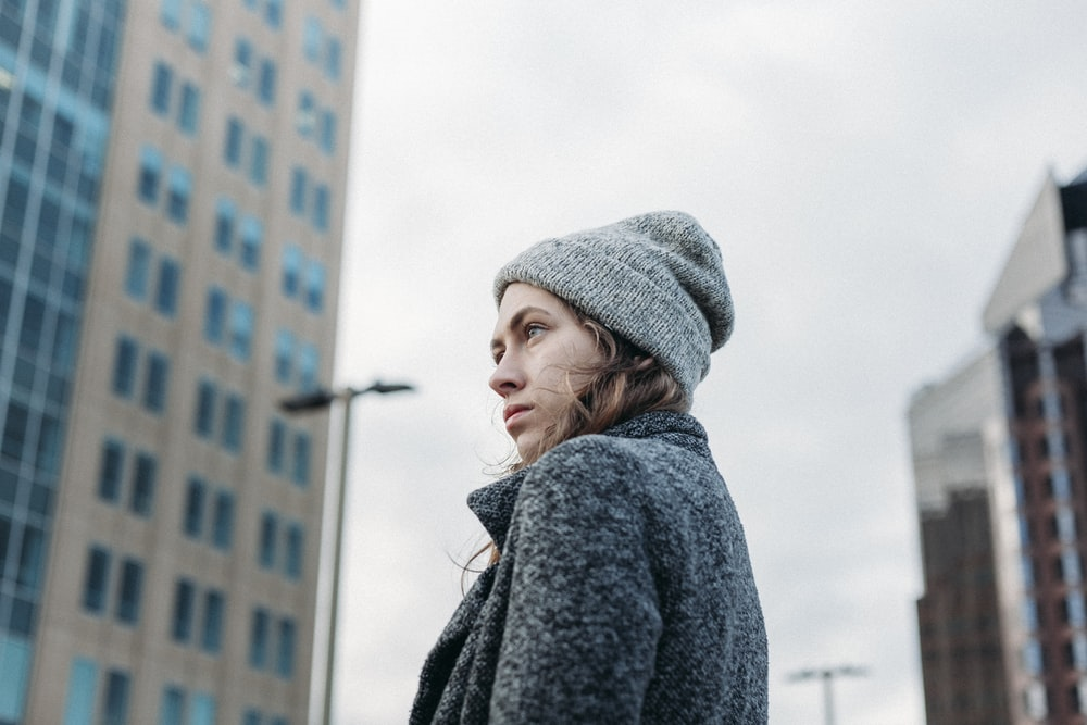 woman wearing gray coat knit cap standing near building during daytime