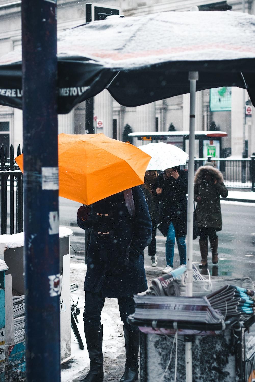 people walking on road while raining