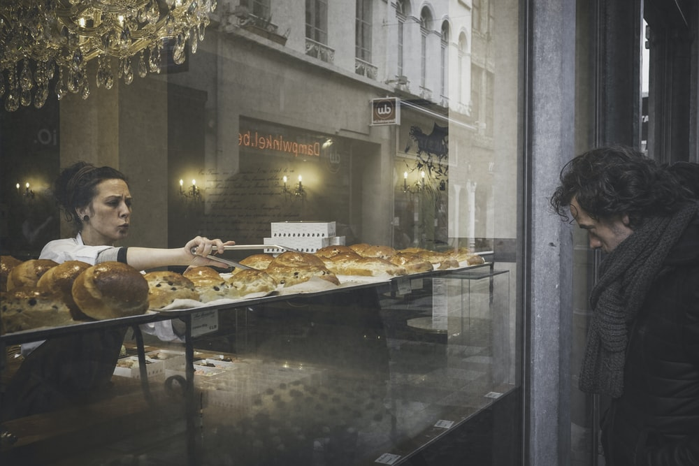 man facing storefront in front of woman holding thong picking bread