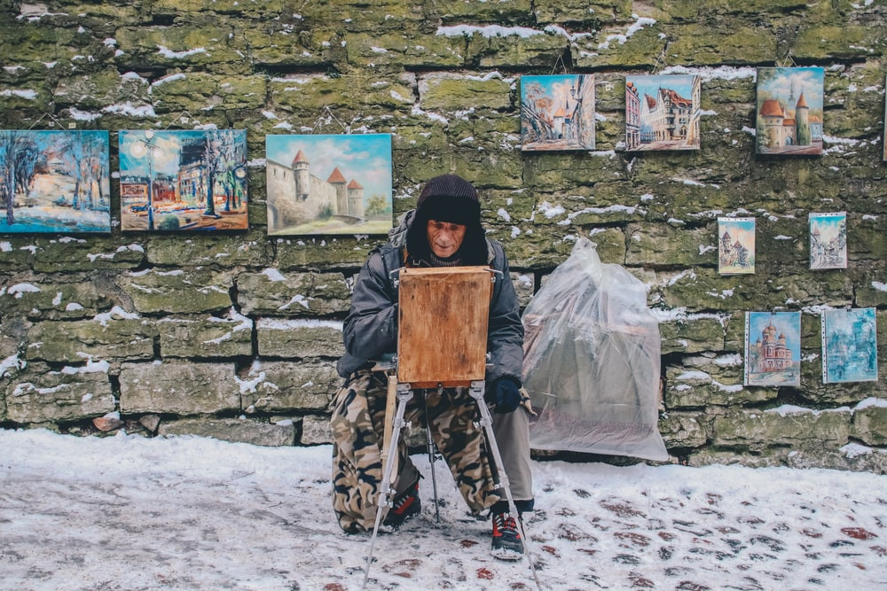 man painting in front of wall with his hanging works