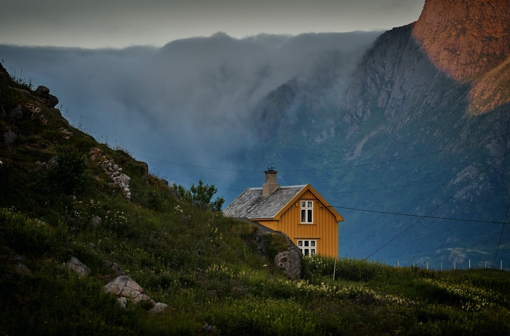 brown concrete house near mountains under white sky at daytime