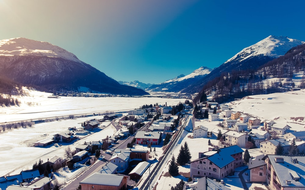 aerial photography of houses covered with snow under blue sky