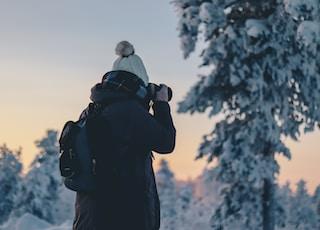 person in black winter jacket holding black DSLR camera during daytime