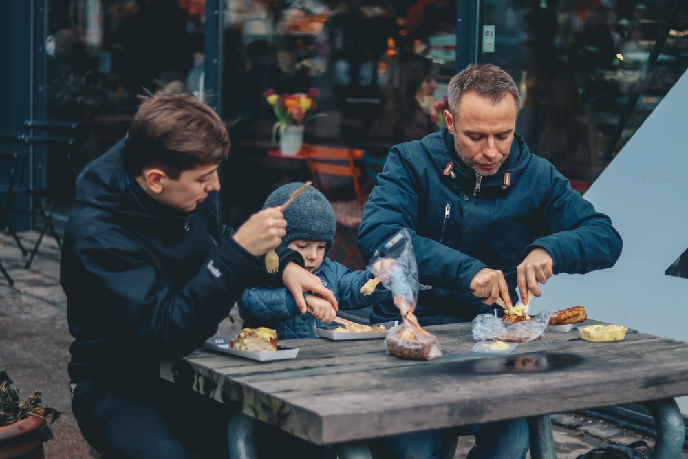 two man and boy sitting in front of table eating