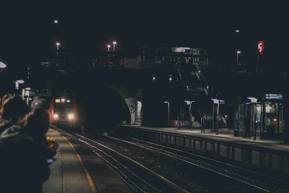 black train under foot bridge