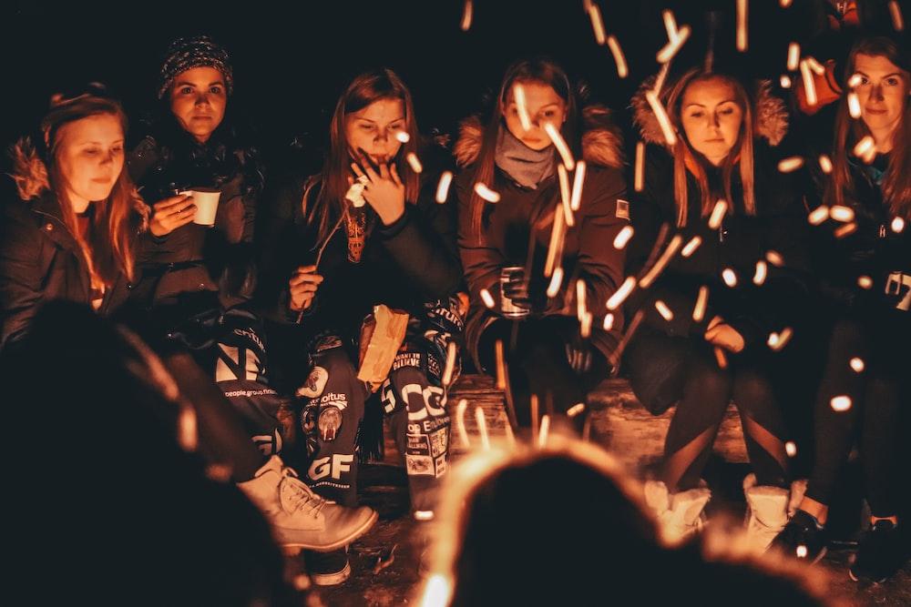 women near bonfire at night